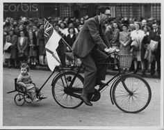 A father on a bicycle tows his small child behind him during V-E Day celebrations near Buckingham Palace, May 8, 1945