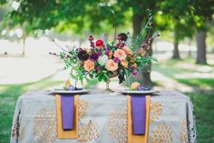 Fall centerpiece.  Orange, red, black, hot pink, purple. Roses, ranunculus, dahlia, ruscus, grapes, hibiscus branches, wheat and other goodies.  Chalice gold container MAXIT FLOWER DESIGN