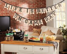 """Draped burlap flag banner spells out """"LIFE IS BETTER ON GAME DAY"""" and attaches with ribbon ties. Hang across a tailgate or at a game day party. Flags: x banner: Game Day Tailgate Banner. Burlap Football, Burlap Flag, Kick Off Football, Pie Game, Wall Banner, Mud Pie, Better Homes And Gardens, Party Games, Party Fun"""