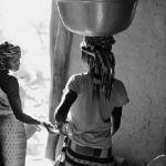 MALI. Dogon region. Yabatalo. Women with water buckets arriving at home. 2009.