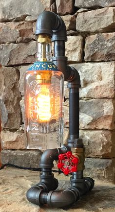 The Cave Dreams Lighting Company Single Desk Light. You can select from our gallery of bottles, request a special bottle or provide one of your own. It is made of industrial pipe and has a working valve as its electrical switch. The light comes with choice of an Edison style bulb or gas lantern style flicker bulb and is equipped with 8 foot cloth covered cord and antique style plug.