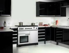 This ultra modern kitchen is definitely a design statment with its sleek black cabinets and smooth silver work tops. Our Professional Deluxe range cooker in White cleverly contrasts making it a desing statement in itself!