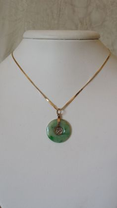 This is a classic jade design piece with some very nice color. Both the pendant and chain are stamped 585 or 14k. The chain was made in Italy. Both pieces are in very good gently worn condition and ha