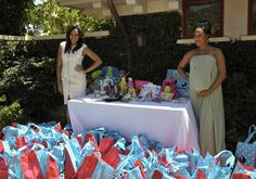 Tia and Tamera Mowry flank a table full of goodies various brands sent in to go in the shower goody bags