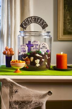 This is one dessert they'll be dying to dig into! Fill a large glass cookie jar with crumbs from your favorite chocolate cake along with white chocolate bones (we used skeleton candy molds from Wilton). Layer in tombstone sugar cookies (we used tombstone and cross cutters) decorated with gray, black, and purple royal icing. Pipe in tufts of grass using green-tinted buttercream. Push in a cemetery sign made from cardstock and painted wood skewers. Tools you'll need: $3, Ske...