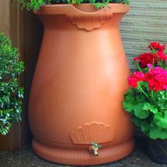 Rain barrel with an urn silhouette with a brass spigot and flat back.    Product: Urn rain barrel  Construction Material: Polyethylene resin  Color: Clay   Features: Urn shape and color add class and style to your rain harvesting   Top functions as a planter which can leech overflow water from the rain barrel  Flat back design sits tightly against any outside wall  Dimensions: 36 H x 25 W x 26 D