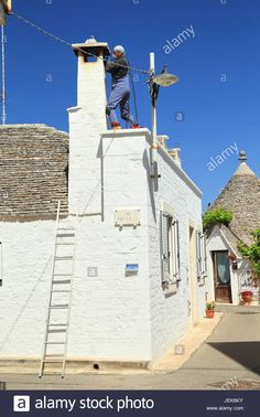 Chimney sweeper at trulli house, Italy Stock Photo