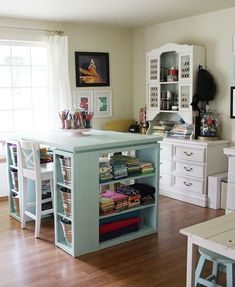 A functional center island is the main attraction in this cozy crafting room. Fabrics are grouped by color and stored without bins or baskets, so they're able to brighten up the room. The light blue and white contrast nicely with the wooden floors.