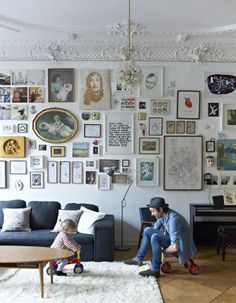 living room, grey sofa, art collage, full walls, family, white walls, white rug, crown moulding