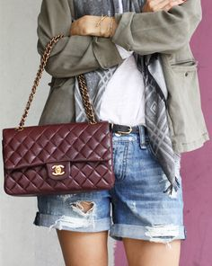 Just The Design: Anine Bing is wearing a pair of light wash denim shorts with a khaki green army jacket from Anine Bing and a burgundy Chanel handbag