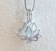 This little lotus locket holds a pretty piece of pale aqua sea glass. A perfect way to carry a bit of the sea with you always. This listing is for a sterling silver lotus locket which includes a sterling silver 16 inch chain. (Picture shown with quarter is of a different piece of sea glass, & is to give you an idea of locket size only.) The lotus flower itself is an aquatic plant represents beauty, enlightenment, spiritual growth, and life itself. It represents the purity of the mind and…