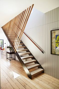 "Visible from many vantage points in the home, beautiful silver ash battens enclose the stairs in the entry hall of this Melbourne home. ""The building designer used slatted timbers extensively outside, so we used slatted timber in various forms inside,"" says interior designer Michelle Skinner of [Designmas](http://www.designmas.com.au/