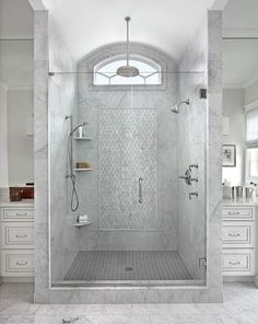 Gray marble tiles lead to a marble walk in shower fitted with a glass door…