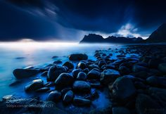 Follow me on my Facebook page or see my Website for more! The rocky coast at Utakleiv beach in Lofoten islands with its famous mountain silhouette in the background. Being a 50s exposure I liked how the movement of the clouds blue color cast and dark tones all created a threatening mood. This image required a great deal of very fine dodging & burning to get the most of the shiny rocks in the foreground and also some additional tricks to make the scene look as I had envisioned it.