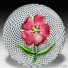 """Antique Saint Louis mauve pelargonium on swirling latticinio paperweight. The delicate flower, with five shaded mauve petals around a yellow, black and green center, blooms atop a green stem with two slender green leaves, over a double-swirl white latticinio cushion. Diameter 2 11/16"""". $ 3,000"""