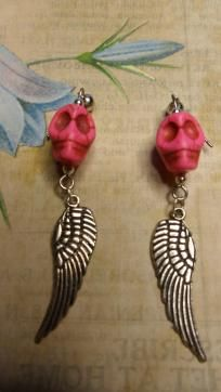 Skulls & Wings Rock Star Earrings  Look like a rock star with this truly unique & cool pair!! This has a hot pink howlite skull bead accented with silver and a large tercel wing with dangles at the bottom. This pair ends with an earring post with r...