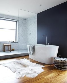 I love the black wall with the marble tile but the timber floor is genius.  Without it, this bathroom would be too cold and clinical.