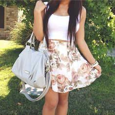 White crop top, antique color floral skirt, and a light gray purse.