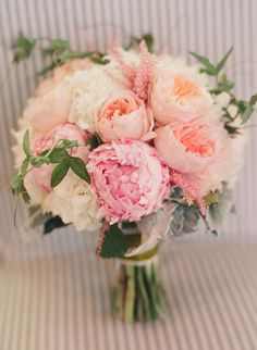 Bouquet made with peach garden roses, light pink peonies, white peonies, white hydrangea, dusty miller, pink astilbe, and passion flower vine