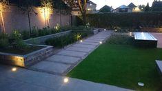 Een mooie tuin door gebruik van materialen door elkaar. Een groot terras van keramiek tegels en een pad van oud gebakken stenen met keramiek tegels erin verwerkt geeft een prachtig uiterlijk. In combinatie met verhoogde borders en lage borders met verschillende beplanting, blijft de tuin speels en is er vanuit elk punt in de tuin...