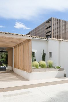 The entrance way has wooden panelling with a few plants e.g. cactus and bushes. The house has a square and rectangle style.