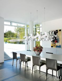 In the dining area of a Richard Meier-designed home, a light fixture designed by Enrico Franzolini and Vicente García Jiménez for Pallucco accents a set of leather-upholstered chairs by Matteograssi.