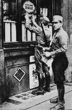Berlin, Germany, SA soldiers hanging an antisemitic sign on a Jewish store.