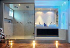 Na suíte do casal, o banheiro é integrado ao quarto, mas tem piso elevado e teto rebaixado. Embutidas no alto e na lateral dessa estrutura de concreto, as luzes azuis de leds criam clima relaxante. A iluminação inclui lâmpadas dicroicas acima das cubas e incandescentes junto ao piso de amêndola. Projeto de Guto Requena