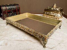 Bandeja para perfumes, taças, decoração.    Esta bandeja certamente deixara seu lugar com mais charme.    Bandeja de mdf com pintura dourado, pés de metal, manta de strass    Bandeja mdf    20 x 30 cm    pés de metal    fundo de espelho    manta de strass