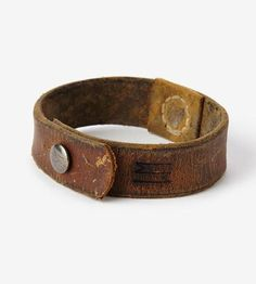 Paying homage to the men who wore them, these leather cuff bracelets are made of vintage military officer coat collars from WWI. The leather is distressed and worn with the kinds of markings only time and use can create, meaning they're already worn-in before affixing to your wrist. Each strap is fitted with a cast brass button closure, to fasten securely onto wrists.