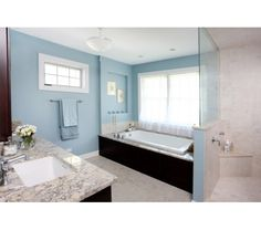Spa like master bathroom with soothing blues, natural stone, and dark stained cabinetry. Like the granite