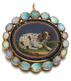 Gold micromosaic and opal brooch, early 19th century The oval micromosaic plaque depicting the profile of a seated spaniel, inset to a lapis lazuli base, framed by a border of cabochon opals.