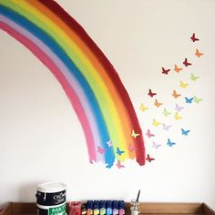 Some tester pots of paint for the rainbow some card cutouts of butterflies painted with leftover paint, some Blu-tack to stick the butterflies to the wall. Cheap but effective wall mural! #rainbows #butterflies #kidsrooms #homedecor #wallmural #DIY #children