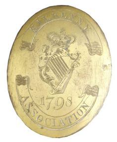 KILKENNY ASSOCIATION, LATE 18TH C IRISH YEOMANRY OR VOLUNTEER INFANTRY SHOULDER BELT PLATE  Oval, gilt on copper, crowned Maid of Erin harp engraved at centre, the date ''1796'' engraved in the field below the harp, twin ribbons above and below bearing the regimental title ''Kilkenny Association'', twin hooks and pair of fixing studs to reverse, c. 1798.  Novelist, Michael Banim, noted that one of the 1798 Kilkenny units paraded in a local churchyard - nicknamed the ''Tombstone Rangers''