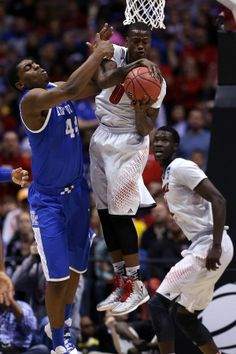 Terry Rozier #0 of the Louisville Cardinals fights for a rebound against Dakari Johnson #44 of the Kentucky Wildcats during the regional sem...