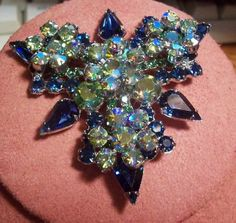 Juiana/DeLizza & Elster Blue Aurora Borealis Brooch  Aurora borealis (those with an iridescent finish) rhinestones were not introduced by Swarovski until the mid-1950s, which helps date many costume pieces
