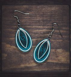 These delicately hand-crafted earrings are made from 1/8 thick deep aqua blue and cream colored quilling strips of paper. I really like the intricate design of this earring that shows the beauty of quilling! The earrings are attached to sterling silver hooks and can also be converted to