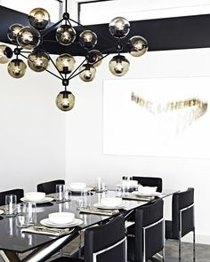 Black and white dining space with modern and luxurious chandelier