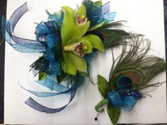 Peacock themed corsage and boutonniere (bout).  The corsage is made with green mini cymbidium orchids, a peacock feather, and double ribbon - blue cosmic ribbon and navy cosmic ribbon.  The boutonniere (bout) is made with a peacock feather, leaves, and a dual ribbon tuck to match the corsage.  By Tillie's Flower Shop  www.tilliesflowers.com