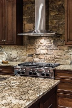 A stainless steel range hood is a sleek, contemporary counterpoint to the stacked stone backsplash. More