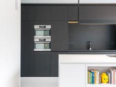Deze moderne rijwoning heeft twee gezichten • Architect: Bettina Luyten (nieuwbouw • keuken • wit keukeneiland • zwarte kasten • inbouwovens)