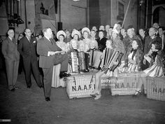 On the stage of Drury Lane theatre, actor manager Sir Seymour Hicks (1871 - 1949) addresses actors who are members of NAAFI, an organisation set up to provide entertainment for the troops during WW II. Chorus girls with accordions are giving a supporting tune.