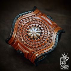 This leather cuff uses the highest quality natural vegetable-tanned leather and is hand tooled with a beautiful stamped border and whipstitched in wide chocolate kangaroo lace. The cuff is shaped in a western border style and airbrushed a beautiful rich russet brown. Applique