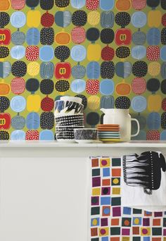 Kompotti Wallpaper A fresh, bold wallpaper featuring a selection of stylised fruits cut in half. Printed in red, teal, blue and yellow on a kiwi ground.