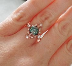 Vintage Inspired Engagement Rings by PenelliBelle ~ The Fountainhead features a 14K rose gold etched antique Art Nouveau style setting. Set with a .80 ct teal blue green moissanite and 0.30 ct of natural full cut bezel set diamonds