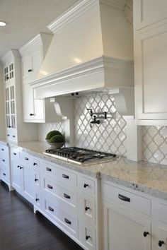 Beautiful kitchen idea with Colonial White granite, white arabesque tile, white cabinets and dark pulls.