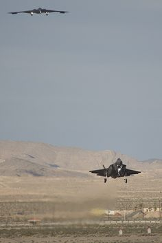 An F-35A lands at Nellis Air Force Base, Nev., with a B-2 bomber flying overhead March 6, 2013. The F-35 was being delivered to Nellis AFB for Operational Test and Evaluation.
