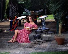 Italian actress Laura Antonelli sitting in a garden leaning on a table. Italy, 1989.