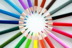 Circle of coloured crayon pencils