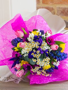 Bright and colourful spring bouquet featuring pink tulips, purple iris, yellow daffodils, cerise anemones, blue hyacinths and white narcissus. Florist based in Lincolnshire and Nottinghamshire.